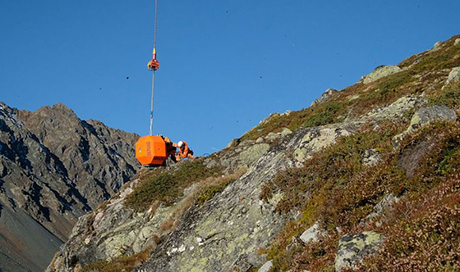 A helicopter transports a block to the release point at the top of the slope. (Photo: Martin Heggli / SLF)