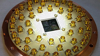 Aide à la correction des erreurs : puce quantique supraconductrice avec 17 qubits montée dans un support avec 48 lignes de contrôle. (Photo: ETH Zurich/Quantum Device Lab)